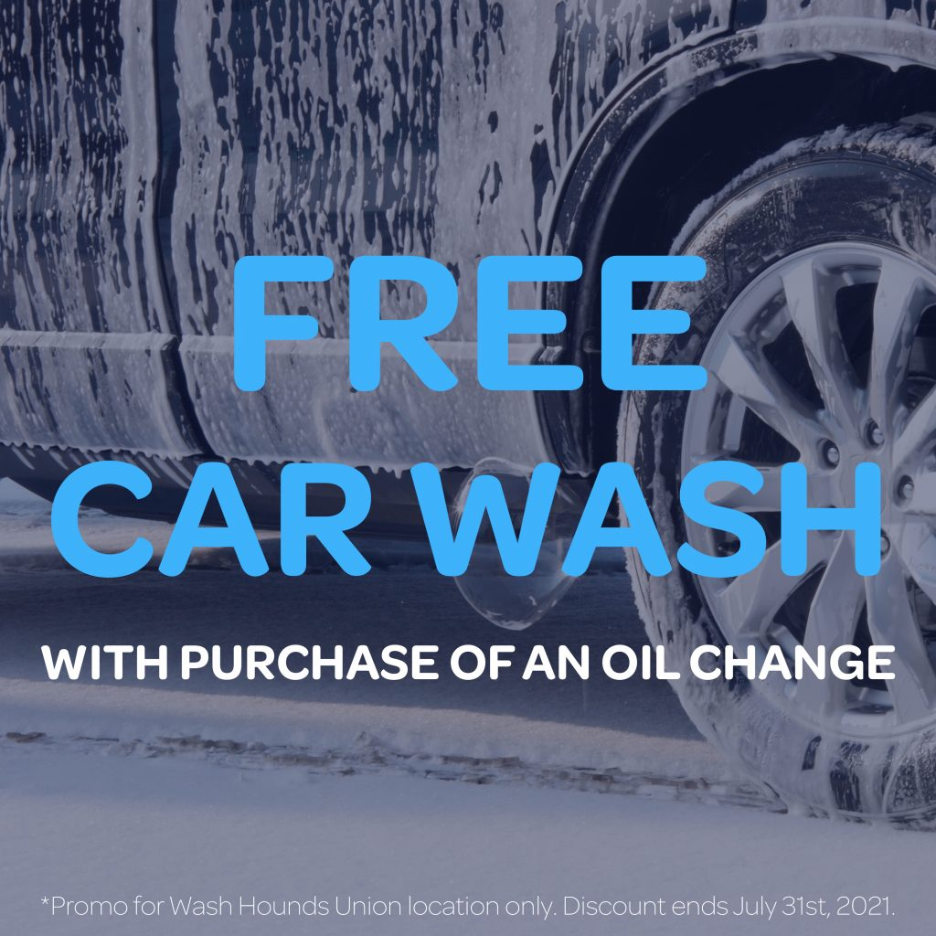 a car with soap and water over its exterior and wheels getting cleaned. free car wash with purchase of an oil change.